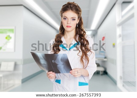 Young beautiful girl intern looking at the x-ray picture of knee in hospital hall - stock photo