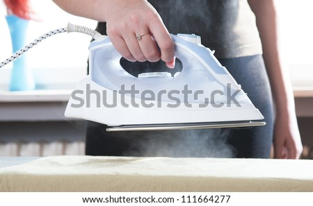 young beautiful girl ironing clothes, with visible steam evaporates - stock photo