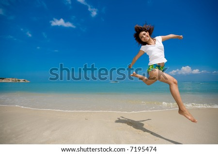young beautiful girl jumping happily at the beach - stock photo