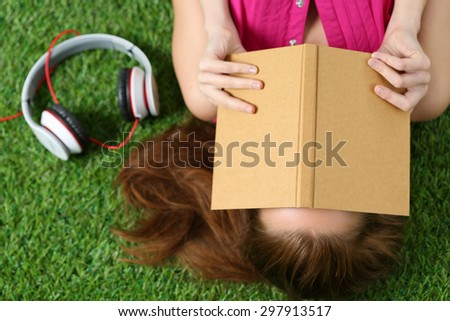 Young beautiful girl laying on the grass in park holding a book. Summertime, leisure and education concept. Top view - stock photo