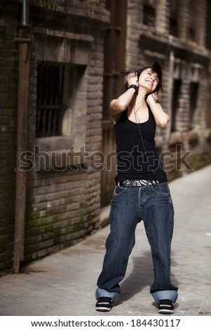 Young beautiful girl listening to music on urban background - stock photo