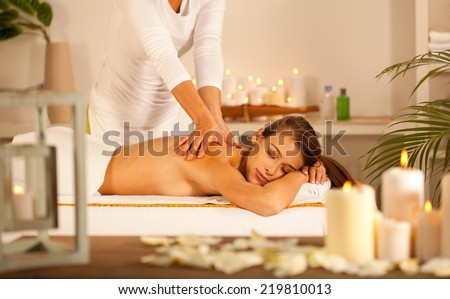 Young beautiful girl lying on massage table and enjoying massage. - stock photo
