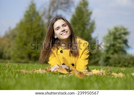 Young beautiful girl lying on the grass in autumn park - stock photo