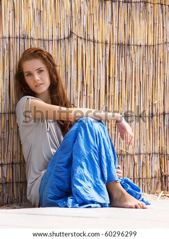 young beautiful girl next to bamboo wall - stock photo