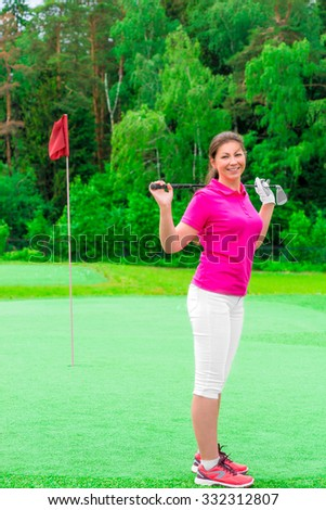 young beautiful girl on a golf course with a golf club - stock photo