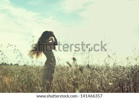 Young beautiful girl on a summer field. Beauty summertime - stock photo