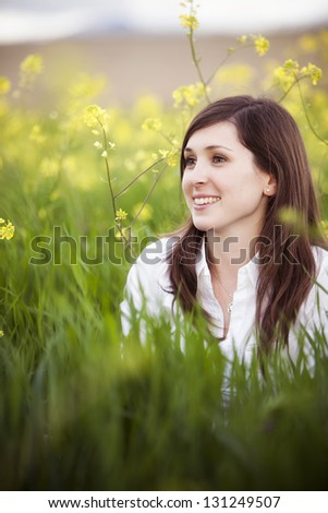 Young beautiful girl on field showing hopeful facial expression - stock photo