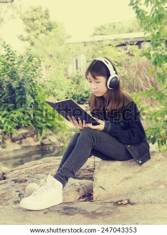 Young beautiful girl reading a book and listen to music in the park - stock photo