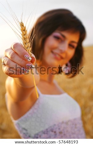 Young beautiful girl showing a corn with her hand - stock photo