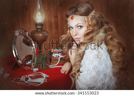 Young beautiful girl sits near a fortune teller desk with a lamp and candles. Card reading. Divination - stock photo