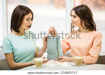 Young beautiful girl sitting in cafe with her friend and receiving a pack with gift. - stock photo