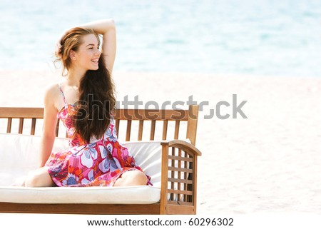 young beautiful girl sitting on beach sofa on sea background - stock photo