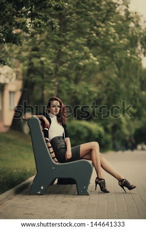 young beautiful girl sitting on bench in park - stock photo