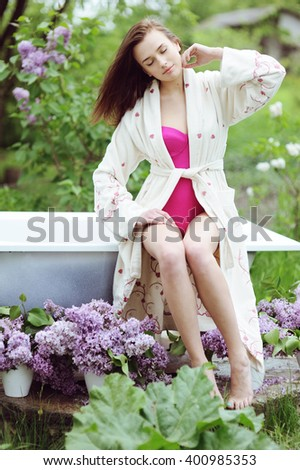 Young beautiful girl sitting on the edge of a bath in the garden - stock photo