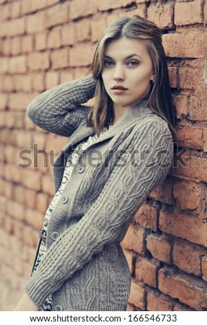 Young beautiful girl standing against the wall - stock photo