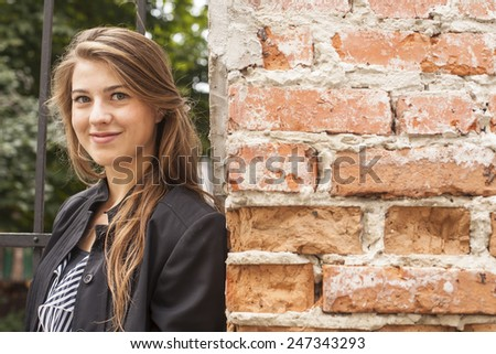 Young beautiful girl standing on a street near the brick wall. Close-up. - stock photo
