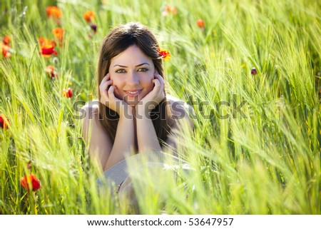 Young beautiful girl staring at camera among green wheat. - stock photo