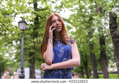 Young beautiful girl talking on mobile in the park. Front bottom view. - stock photo
