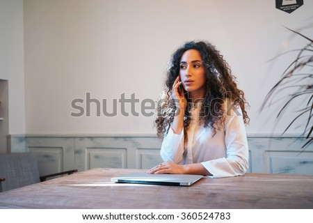 Young beautiful girl talking on the phone and working with a laptop in a coffee-shop.  - stock photo