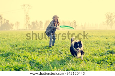 Young beautiful girl throwing frisbee to her dog in a park at sunset - Asian woman playing with her dog - stock photo