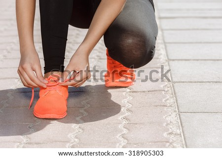Young beautiful girl tying her laces outdoors - stock photo