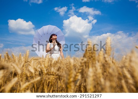 Young beautiful girl walk through golden field of wheat with white umbrella and enjoy life - stock photo