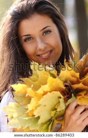 young beautiful girl with a bouquet of maple leaves - stock photo