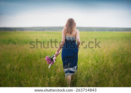 Young beautiful girl with a bouquet of peonies is in the field,concept - stock photo