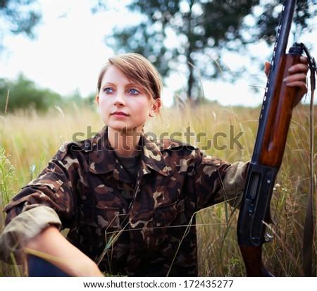 Young beautiful girl with a shotgun outdoor - stock photo