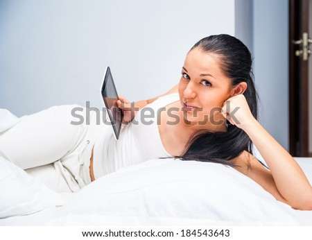 young beautiful girl with a tablet at home in white bed - stock photo