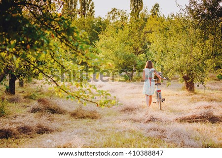 Young beautiful girl with a vintage bike in the park - stock photo