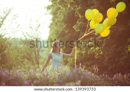 young beautiful girl with baloons in the field of flowers - stock photo