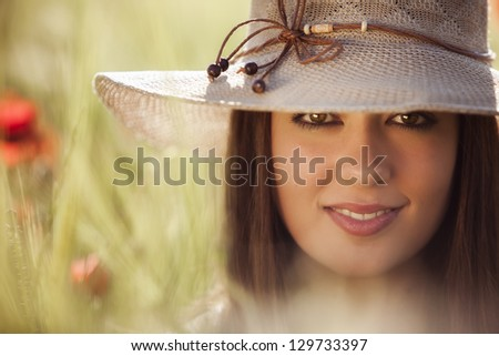 Young beautiful girl with hat staring and smiling at camera - stock photo