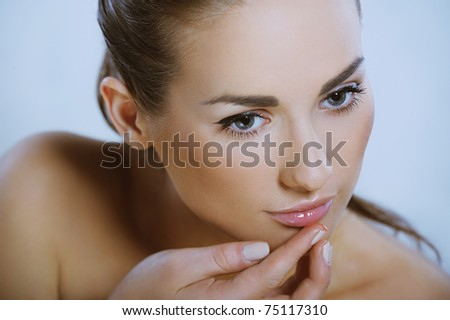 young beautiful girl with healthy skin puts gloss on her lip - stock photo