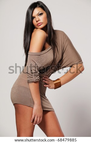 Young beautiful girl with long black hair in gray dress. - stock photo