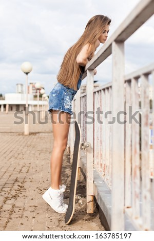 young beautiful girl with long legs and silky hair in denim short overalls stands on tiptoes hanging over bridge - stock photo