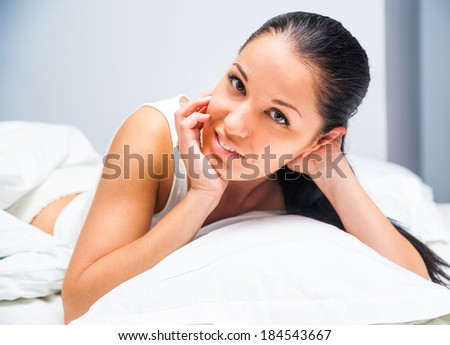 young beautiful girl woke up at home in white bed - stock photo