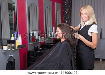 Young beautiful hairdresser working in beauty salon - stock photo