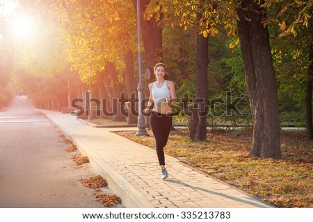 young beautiful happy and sexy runner girl with nice body in the autumnal colored park. with sun on backlight is looking at camera with happiness and smile with white sport suit. - stock photo