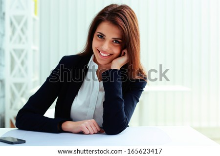 Young beautiful happy businesswoman sitting at the table in office - stock photo