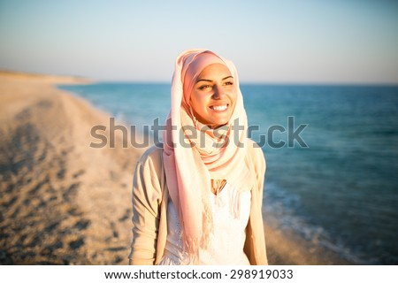 Young beautiful happy muslim woman outdoors portrait.Seaside,beach walk.Beautiful arab saudi woman face posing on the beach with the sea in the background - stock photo
