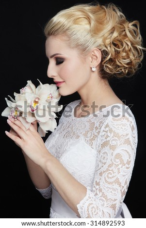 Young beautiful happy slim blonde bride in lacy dress with stylish prom hairdo - stock photo