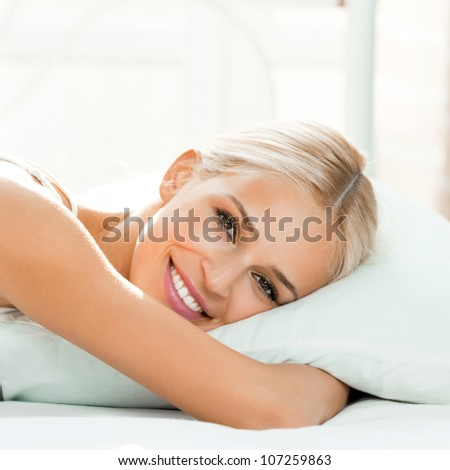Young beautiful happy smiling blond woman waking up on bed - stock photo