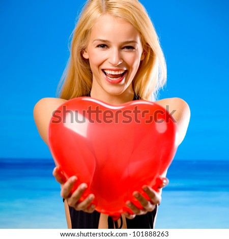Young beautiful happy smiling cheerful blond woman on beach, holding valentine's balloon - stock photo