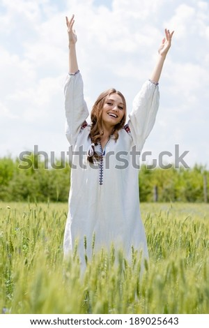 Young beautiful happy smiling woman blond girl in traditional Ukrainian dress standing hands up to sky relaxing in wheat field on summer day outdoors background portrait - stock photo