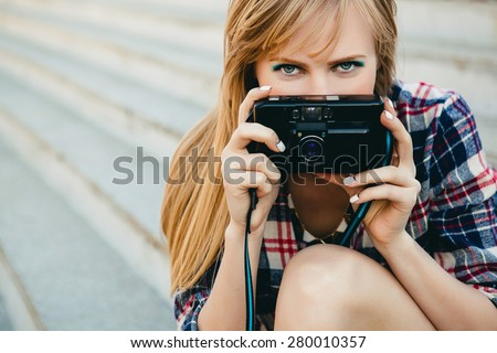 young beautiful happy stylish hipster girl, denim outfit, flirty happy, cool vintage style, having fun, sitting, stairs, oldschool film camera, take photo, eyes, close up, hands holding, looking - stock photo