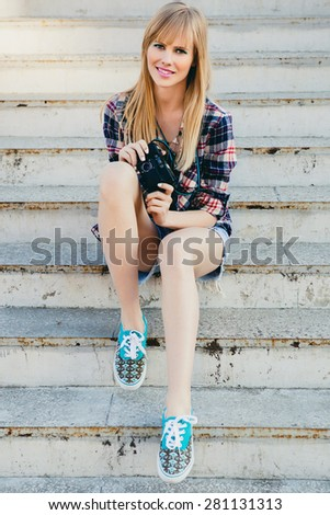 young beautiful happy stylish hipster girl, denim outfit, flirty happy, cool vintage style, having fun, sitting, stairs, oldschool film camera, take photo, hands holding, blond, sneakers, smiling - stock photo