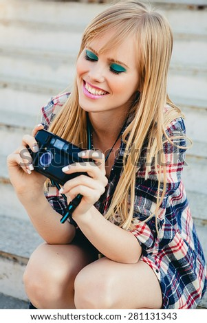 young beautiful happy stylish hipster girl, denim outfit, flirty happy, cool vintage style, having fun, sitting, stairs, oldschool film camera, take photo, hands holding, blond, close up, smiling - stock photo
