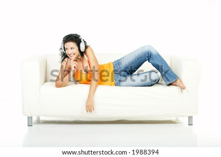 Young beautiful happy women listening music in headphones on white couch - stock photo