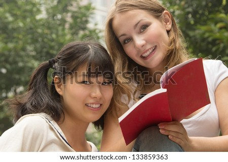 Young beautiful happy women reading book at city park. Girls smiling and have fun outdoor - stock photo